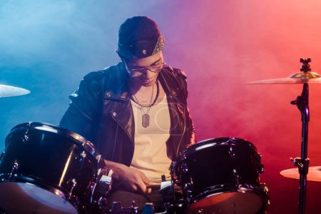 smiling young male musician in leather jacket playing drums during rock concert on stage with smoke and dramatic lighting
