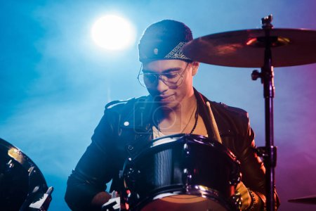 mixed race man in leather jacket playing drums during rock concert on stage with smoke and spotlight