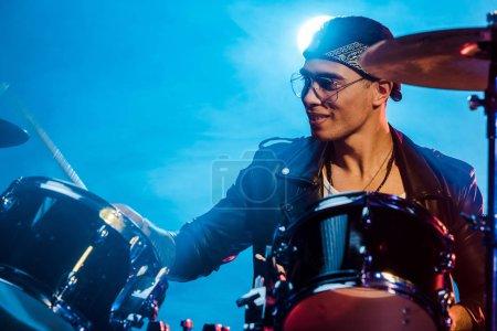 Photo pour Joyeux musicien masculin en veste de cuir jouant de la batterie lors d'un concert de rock sur scène avec de la fumée et des projecteurs - image libre de droit
