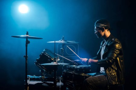 side view male musician in leather jacket playing drums during rock concert on stage with smoke and spotlight