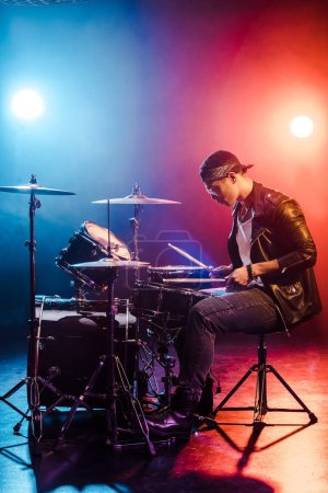 male rock star in leather jacket playing drums during concert on stage with smoke and spotlights