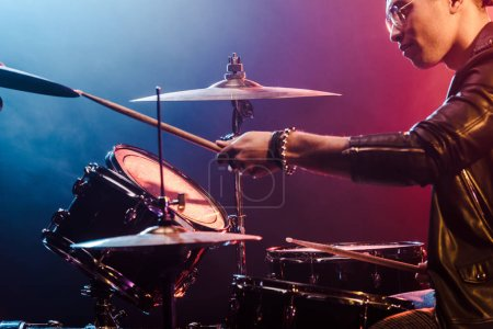 mixed race male musician in leather jacket playing drums during rock concert on stage with smoke and dramatic lighting