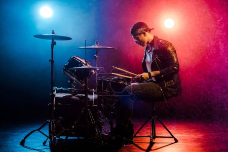 Photo for Side view of male musician in leather jacket playing drums during rock concert on stage with smoke and spotlights - Royalty Free Image