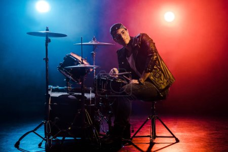 young mixed race male musician sitting behind drum set on stage with spotlights and smoke