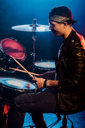 happy male musician in leather jacket playing drums during rock concert on stage with smoke and dramatic lighting