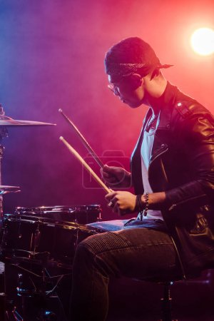 side view of male musician in leather jacket playing drums during rock concert on stage with smoke and dramatic lighting