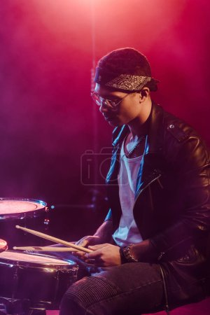 male musician in leather jacket playing drums during rock concert on stage with smoke and dramatic lighting
