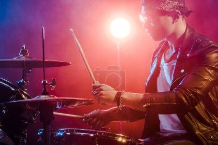Photo pour Vue latérale du jeune musicien en veste de cuir jouant de la batterie lors d'un concert de rock sur scène - image libre de droit
