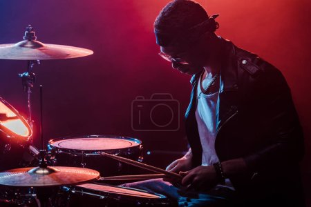 mixed race male musician in leather jacket playing drums during rock concert on stage