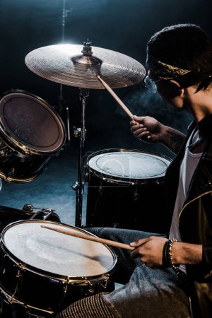 Photo for Side view mixed race male musician playing drums during rock concert on stage - Royalty Free Image