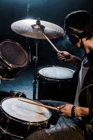 Photo pour Musicien mâle de race mixte vue de côté jouer de la batterie pendant le concert de rock sur scène - image libre de droit