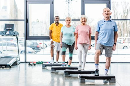 Photo for Happy multiethnic senior athletes standing near step platforms at gym - Royalty Free Image