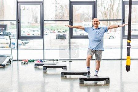 Photo for Cheerful senior sportsman exercising on step platform at gym - Royalty Free Image
