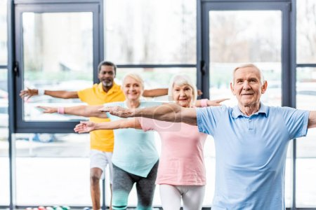 Photo for Multicultural senior athletes synchronous doing exercise at gym - Royalty Free Image