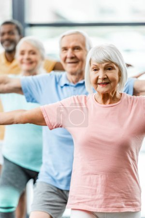 Photo for Selective focus of senior sportspeople synchronous doing exercise at gym - Royalty Free Image