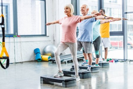 Photo for Multicultural senior athletes synchronous exercising on step platforms at sports hall - Royalty Free Image