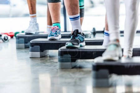 Photo for Partial view of sportspeople doing exercise on step platforms at gym - Royalty Free Image