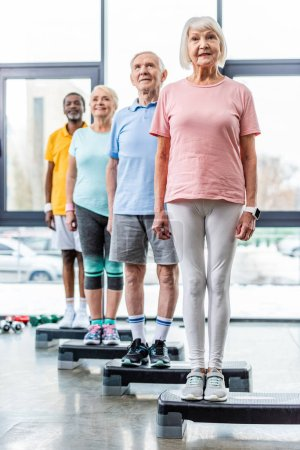 Photo for Cheerful multiethnic senior athletes standing on step platforms at gym - Royalty Free Image
