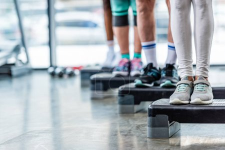 cropped shot of sportspeople standing on step platforms at gym