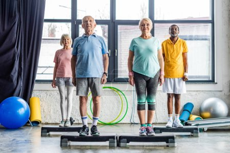 Photo for Multiethnic senior athletes synchronous exercising on step platforms at gym - Royalty Free Image