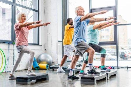 Photo for Senior athletes synchronous exercising on step platforms at gym - Royalty Free Image