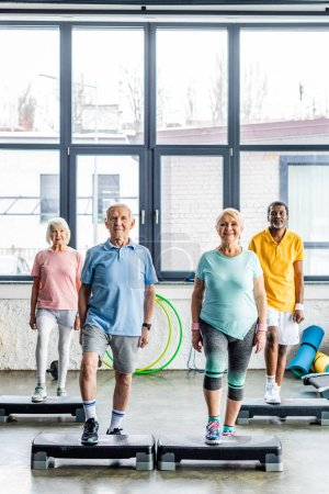 Photo for Happy multicultural senior athletes synchronous exercising on step platforms at gym - Royalty Free Image