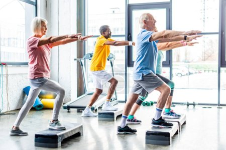 Photo for Side view of multicultural senior athletes synchronous exercising on step platforms at gym - Royalty Free Image