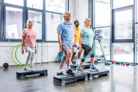 Photo for Senior multicultural athletes synchronous exercising on step platforms at gym - Royalty Free Image
