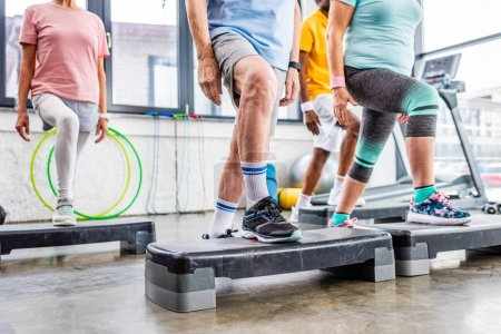 Photo for Cropped shot of senior athletes synchronous exercising on step platforms at gym - Royalty Free Image