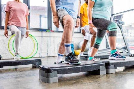 cropped shot of senior athletes synchronous exercising on step platforms at gym