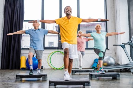 Photo for Smiling senior multicultural athletes synchronous exercising on step platforms at gym - Royalty Free Image
