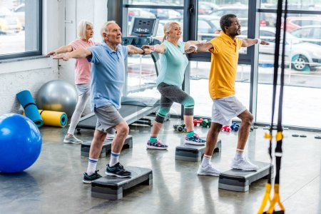 Photo for Selective focus of senior multicultural athletes synchronous exercising on step platforms at gym - Royalty Free Image