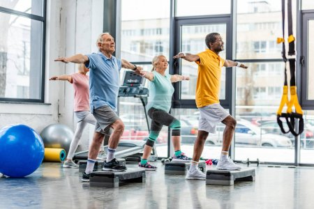 multicultural senior sportspeople synchronous exercising on step platforms at gym