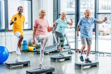 Photo for Smiling multiethnic senior athletes synchronous exercising on step platforms at gym - Royalty Free Image