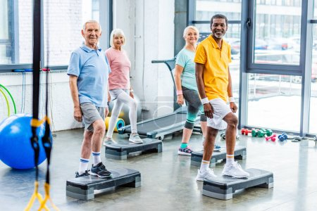 multiethnic senior athletes synchronous exercising on step platforms at gym