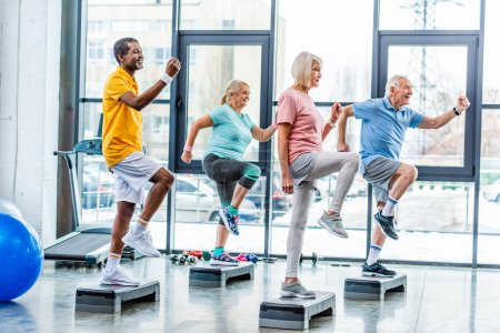 Photo for Side view of multiethnic senior athletes synchronous exercising on step platforms at gym - Royalty Free Image