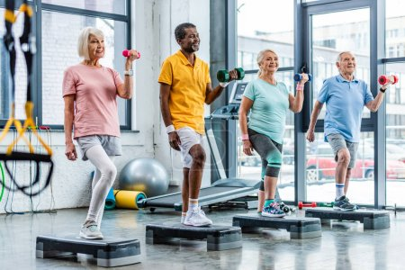 Photo for Smiling senior multicultural sportspeople synchronous exercising with dumbbells on step platforms at gym - Royalty Free Image
