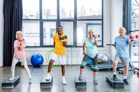 Photo for Happy senior multicultural sportspeople synchronous exercising with dumbbells on step platforms at gym - Royalty Free Image