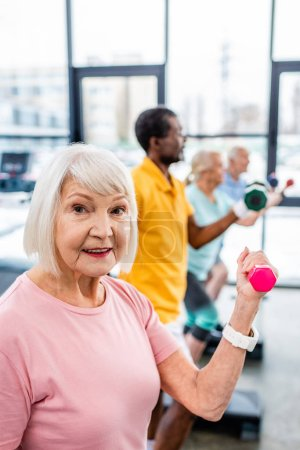 selective focus of senior woman and her friends exercising with dumbbells at gym