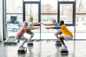 multicultural senior athletes synchronous doing squats on step platforms at gym
