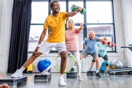Photo for Selective focus of senior multicultural sportspeople synchronous exercising with dumbbells on step platforms at gym - Royalty Free Image