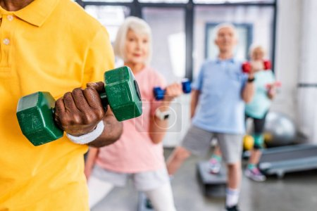 partial view of senior sportspeople synchronous exercising with dumbbells at gym