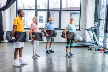 Photo for Multicultural senior sportspeople holding step platforms at gym - Royalty Free Image