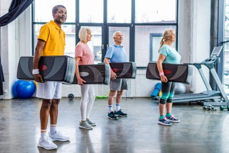 Photo for Senior multiethnic sportspeople holding step platforms at gym - Royalty Free Image