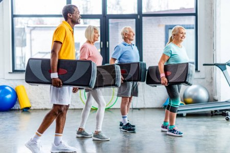 Photo for Happy multiethnic sportspeople holding step platforms at gym - Royalty Free Image