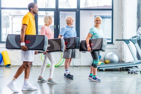 Photo for Multiethnic senior sportspeople holding step platforms at gym - Royalty Free Image