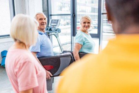 selective focus of senior sportspeople holding step platforms at gym