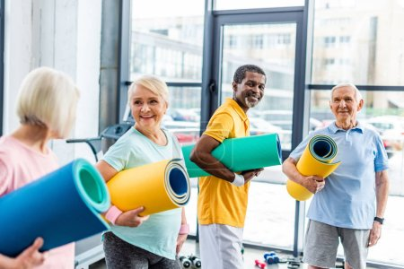 smiling multethnic senior athletes holding fitness mats at sports hall
