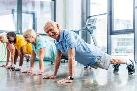 Photo for Happy multiethnic senior sportspeople synchronous doing plank at gym - Royalty Free Image