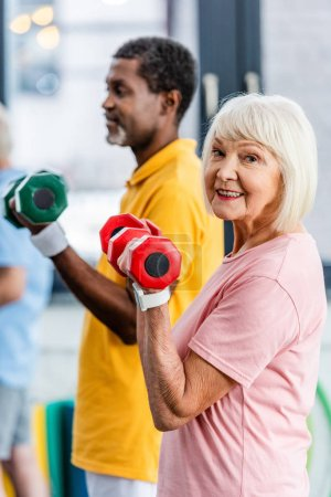 selective focus of senior woman and her african american husband doing exercise with dumbbells at gym